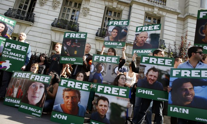 Greenpeace activists protest on Sept. 27 in front of the Russian embassy in Paris, with signs calling for the release of 30 activists from 18 countries arrested while protesting against the extraction of oil in the Arctic. One Australian citizen, Colin Russell, and another Australian resident are among the activists held without charges in a Russian prison. (Thomas SamsonAFP/Getty Images)