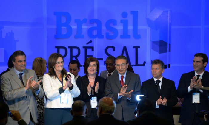 (L-R) Brazil's Justice Minister Jose Eduardo Cardozo, Petrobras' President Maria das Gracas Silva Forster, National Oil Agency (ANP) Director General Magda Chambriard and Mines and Energy Minister Edson Lobao celebrate the end of the Libra auction in Rio de Janeiro, Brazil, Oct. 21. (VANDERLEI ALMEIDA/AFP/Getty Images)