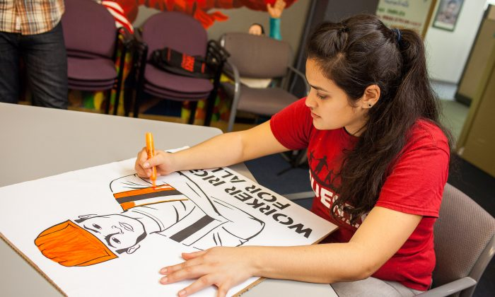 Volunteers work on signs and banners in preparation for an immigration march on Saturday, Oct. 5. (Petr Svab/Epoch Times)