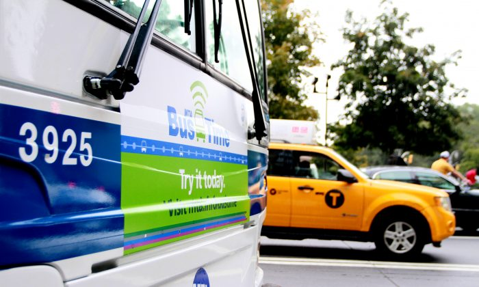 A bus with a sign promoting the MTA Bus Time real-time bus tracking service stands on Columbus Circle in New York City, Oct. 7, 2013. (Ivan Pentchoukov/Epoch Times)