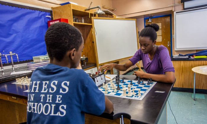 Youth play chess during the first round of the Columbus Day Tournament in Frederick Douglass Academy in New York City on Oct. 14, 2013. (Petr Svab/Epoch Times)