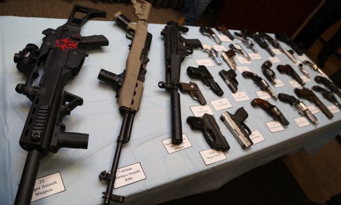 Illegally trafficked guns, including rifles, revolvers and pistols, displayed at the Kings County District Attorney's Office, in Brooklyn on Oct. 16, 2013. (Christian Watjen/The Epoch Times)