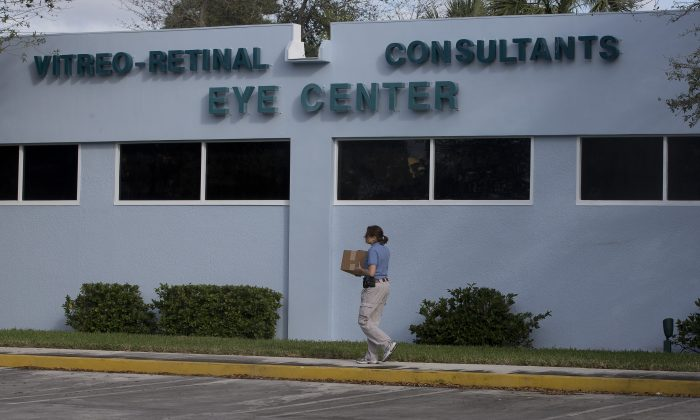An FBI agent carries a box of equipment into the Vitreo-Rential Consultants Eye Center in West Pam Beach, Fla., Wednesday, Jan. 30 2013 as other FBI agents continue to search the medical office of prominent South Florida political donor Dr. Salomon Melgen. (AP Photo/J Pat Carter)
