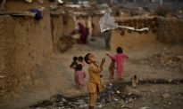 Afghan refugee boy plays with a kite
