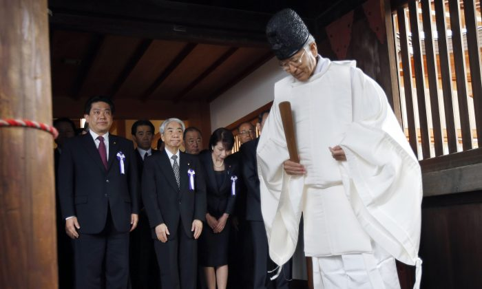 A group of Japanese lawmakers are led by a Shinto priest at the Yasukuni Shrine in Tokyo during an annual autumn festival in Tokyo, Friday, Oct. 18, 2013. (AP Photo/Koji Sasahara)