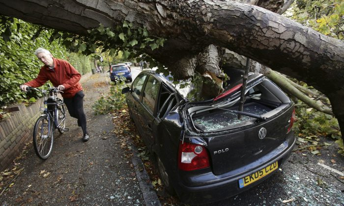 A car is crushed under a fallen tree as a man pushes a bicycle nearby following a storm, in Hornsey, north London, Monday Oct. 28, 2013. A major storm with hurricane-force winds is lashing southern Britain, causing flooding and travel delays including the cancellation of roughly 130 flights at London's Heathrow Airport. (AP Photo/PA, Yui Mok)