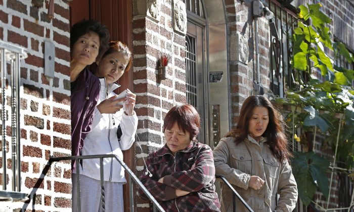 Women gather on the steps of an apartment building opposite the scene of a brutal fatal stabbing in Sunset Park, Brooklyn, New York, Oct. 27, 2013. (Kathy Willens/AP)