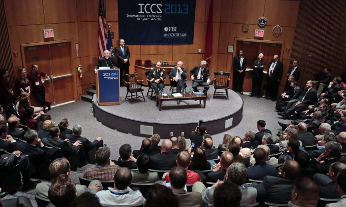 President of Fordham University the Rev. Joseph Michael McShane speaks at the International Conference on Cyber Security (ICCS), Aug. 8 at Fordham University in New York, while the directors of the NSA, CIA, and FBI are seated on stage. Chinese spies target conferences for espionage, due to the value of information available and high-level people who attend.(AP Photo/Bebeto Matthews)