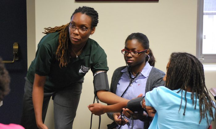 Renée Volny, OB/GYN, shows students how to read a blood pressure meter at the Tour for Diversity in Medicine at the Georgetown University School of Medicine, Sept. 28. (Ron Dory/Epoch Times)