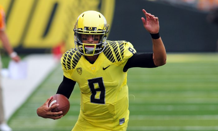 Oregon quarterback Marcus Mariota runs with the ball during an NCAA college football game against Tennessee in Eugene, Ore. Mariota and the Ducks face Washington. (AP Photo/Steve Dykes)