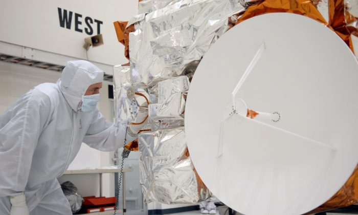 A Ball Aerospace technician looks over NASA's Kepler spacecraft, during a media event at the Astrotech Space Operations facility in Titusville, Fla. in 2009. An upcoming conference on the Kepler Space Telescope has aroused controversy, due to the U.S. government policy of excluding Chinese nationals. (NASA/Troy Cryder)