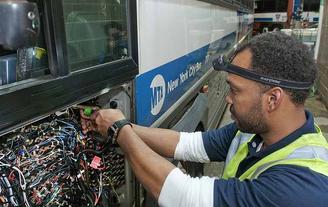 A technician installs GPS and related equipment for the MTA Bus Time service on an MTA bus, Nov. 2011. (Patrick Cashin/Metropolitan Transportation Authority)