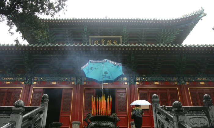 Dengfeng, CHINA: A tourist walks to a shrine at Shaolin Temple on Songshan Mountain, in Henan Province, on Aug. 25, 2006. The Temple was built in AD 495 and is considered the birthplace of Shaolin Kung Fu. (China Photos/Getty Images)