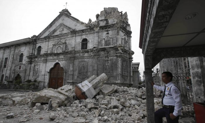 A guard stands near the damaged Basilica of the Holy Child following an earthquake that hit Cebu City in the central Philippines, Oct. 15. (AP Photo/Bullit Marquez)