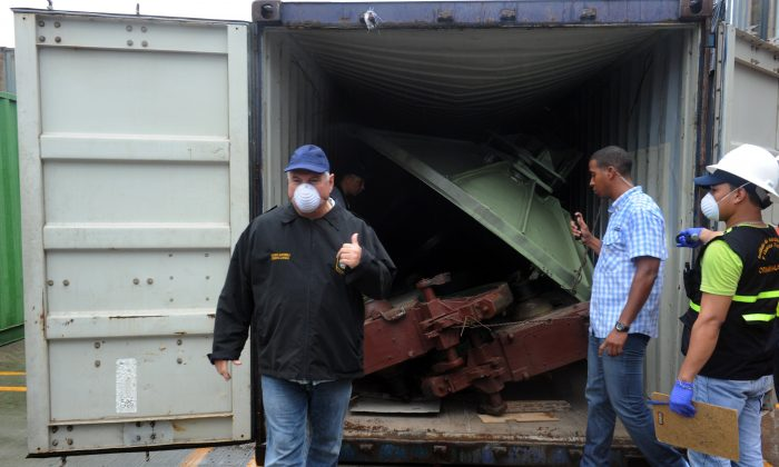 Panamanian President Ricardo Martinelli (L) gestures toward a container with the MIG-21 jets found inside the North Korean vessel where an alleged Soviet-built radar control system for surface-to-air missiles was found, at the Manzanillo Port in Colon, 90 km from Panama City, on July 21. (Rodrigo Arangua/AFP/Getty Images)