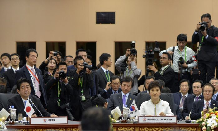 Japanese Prime Minister Shinzo Abe (L) and South Korean President Park Geun-hye (C) at the 16th ASEAN Plus Three (China, Japan, South Korea) summit on Oct. 10. (Philippe Lopez/AFP/Getty Images)