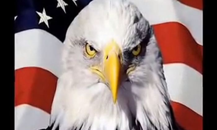 """A screenshot of the film """"Silent Battle"""" from the National Defense University,  shows a tough-looking eagle, representing America, with the national flag of the United States in the background. The documentary says that the United States is China's enemy, despite American policy that attempts to prove the contrary. (Screenshot from National Defense University)"""