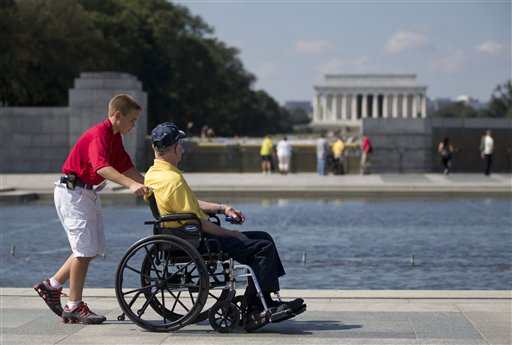 Korean War veteran Robert Olson, from Iowa, is pushed in his wheelchair by Zach Twedt, also from Iowa, around the National World War II Memorial in Washington, Tuesday, Oct. 1, 2013. Veterans who had traveled from across the country were allowed to visit the National World War II Memorial after it had been officially closed because of the partial government shutdown. After their visit, the National World War II Memorial was closed again. The Lincoln Memorial is seen in the distance. (AP Photo/Carolyn Kaster)