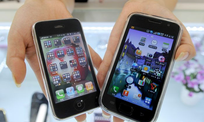 A South Korea shop manager shows Samsung Electronic's Galaxy S mobile phone (R) and Apple's iPhone 3G, July 27, 2010. (PARK JI-HWAN/AFP/Getty Images)