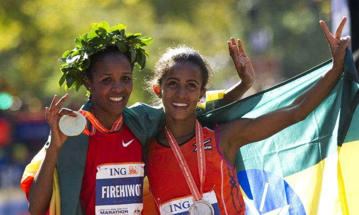 Firehiwot Dado with her friend Buzunesh Deba, both of Ethiopia, celebrate after finishing first and second place, respectively, in the 42nd ING New York City Marathon on Nov. 6, 2011. (Don Emmert/Getty Images)