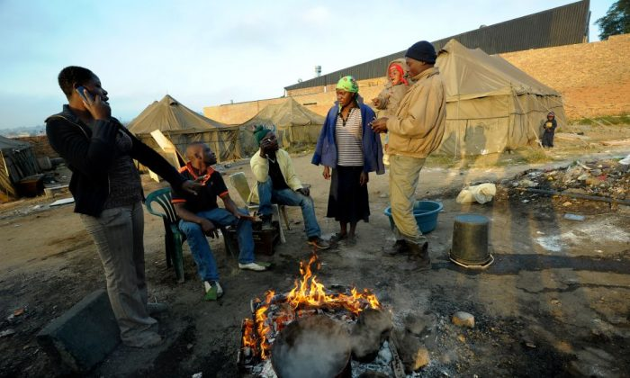 A group of homeless people warm up around a fire in Alexandra township in Johannesburg, South Africa, on July 11, 2013 as the country commemorates 50 years since the police raid on a Johannesburg Rivonia farm where top leaders from Nelson Mandela's African National Congress were arrested. Former South African President and anti-apartheid hero Nelson Mandela is still hospitalized in a critical but stable condition after his June 8 admittance for an obstinate pulmonary infection. (AFP PHOTO / ALEXANDER JOE)