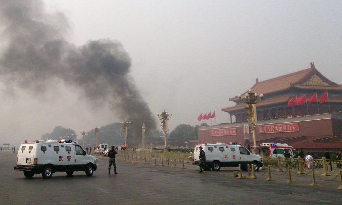 Police cars block off the roads leading into Tiananmen Square as smoke rises into the air after a vehicle crashed in front of Tiananmen Gate in Beijing on Oct. 28, 2013. The car was driven by a Uyghur, and Uyghurs fear this incident will be used by the Chinese regime to justify harsh suppression. (STR/AFP/Getty Images)