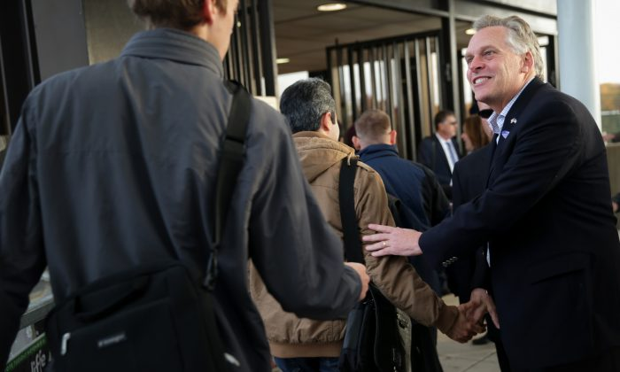 Democratic Virginia gubernatorial candidate Terry McAuliffe (R) greets commuters at Vienna/Fairfax-GMU Metro Station in Fairfax, Va. on Election Day, Nov. 5. He won a narrow victory. (Alex Wong/Getty Images)