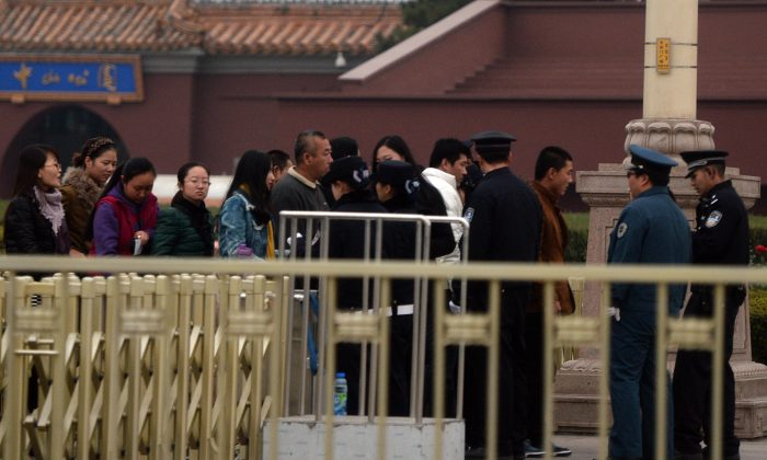 Chinese police check tourists entering Tiananmen Square as security is increased during the Communist Party Central Committee's Third Plenum in Beijing on Nov. 9, 2013. The four-day session takes place in a hotel in the capital's outskirts that in 1978 hosted the plenum that set the country on the path of Deng Xiaoping's economic reforms. (Mark Ralston/AFP/Getty Images)