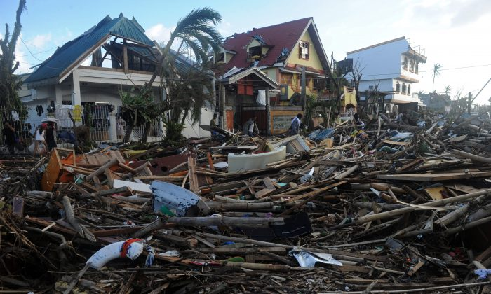 People walk among debris and destroyed houses in Palo, eastern island of Leyte on November 10, 2013, three days after devastating Super Typhoon Haiyan hit the area on November 8. The death toll from a super typhoon that decimated entire towns in the Philippines could soar well over 10,000, authorities warned on November 10, making it the country's worst recorded natural disaster.  (Noel Celis/AFP/Getty Images)