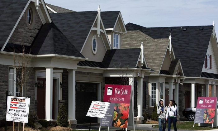 People walk past homes for sale in Oakville, Ont., in this file photo. The IMF says CMHC mortgage insurance exposes the government to financial system risks and might distort the market as a whole in favour of mortgages over more productive uses of capital. (The Canadian Press/Nathan Denette)