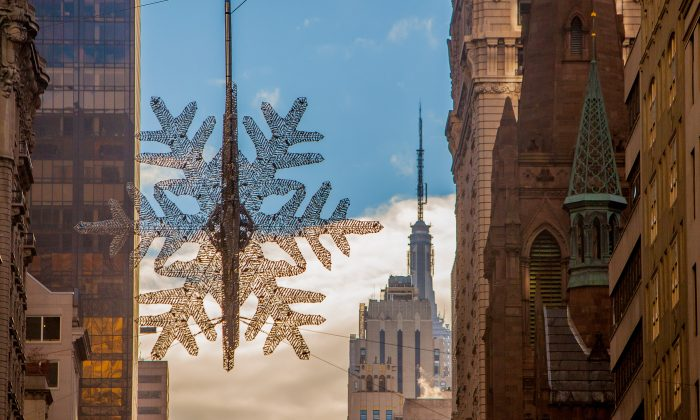 The UNICEF giant crystal and aluminum snowflake was hoisted above Fifth Avenue and 57 Street in Manhattan, New York, on Nov. 3, 2013. (Petr Svab/Epoch Times)