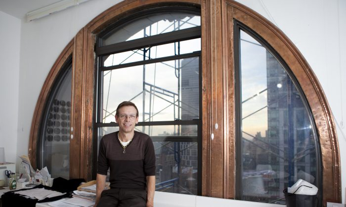 Jeweler Ray Griffiths in front of the arched copper window that drew him to his current 5th Avenue studio that he restored to its original color. (Samira Bouaou/Epoch Times)