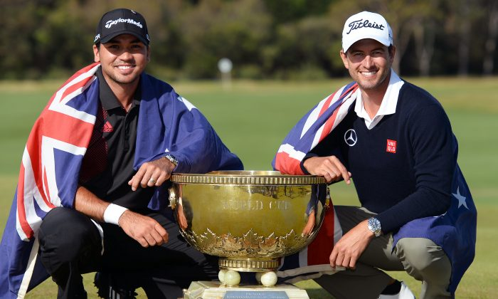 Jason Day (L) and Adam Scott (R) of Australia pose with the trophy after winning the team event of the Golf World Cup tournament played at the Royal Melbourne course in Melbourne, on Nov. 24, 2013. (William West/AFP/Getty Images)