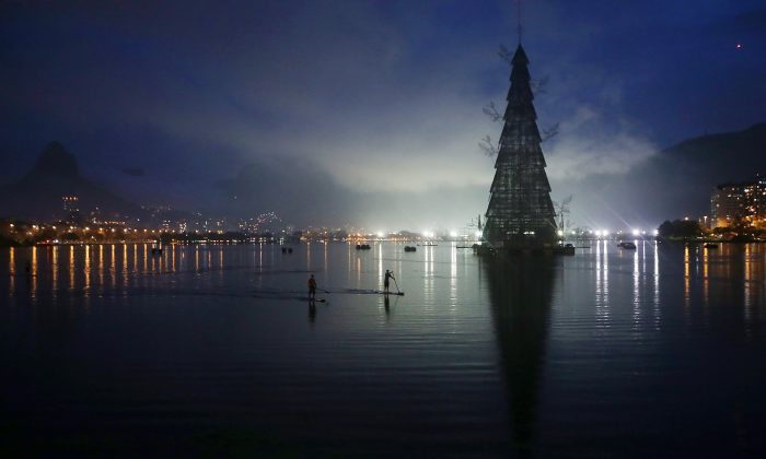 DEC 1: Stand-up paddle boarders row past before the lighting ceremony for Rio de Janeiro's famed floating Christmas tree in Lagoa Rodrigo de Freitas on November 30, 2013 in Rio de Janeiro, Brazil. The constructed tree is the largest floating Christmas tree in the world according to the Guinness Book of World Records. The tree is 85 meters tall and is displayed by three million microlights. (Mario Tama/Getty Images)