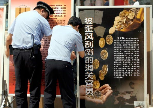 Chinese policemen set up anti-corruption billboards in Central Beijing, June 11, 2007. (Teh Eng Koon/AFP/Getty Images)
