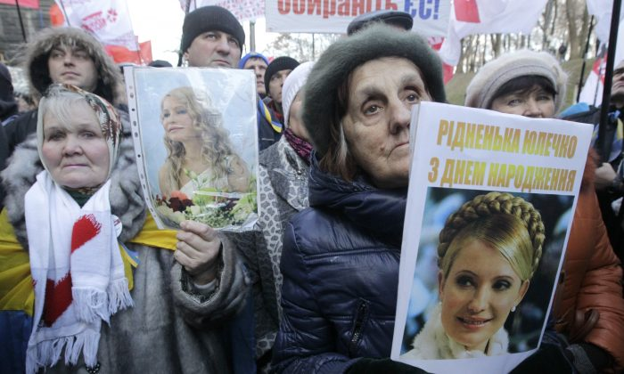 Activists of the Ukrainian Opposition Party hold a posters with a photo of former Ukrainian Prime Minister Yulia Tymoshenko  during a rally in front of the Ukrainian Cabinet of Ministers in Kiev, Ukraine, Wednesday Nov. 27, 2013.  Tymoshenko celebrates her 53rd birthday today. (AP Photo/Sergei Chuzavkov)