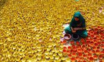 Indian potter paints earthen lamps