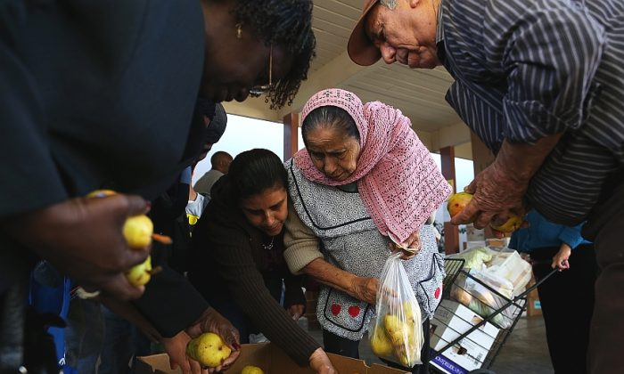 People pick through a box of pears as they wait in line at a food bank on November 1, 2013. An estimated 47 million Americans will see their food stamp benefits cut starting this month, and deeper cuts to the program are expected soon. (Justin Sullivan/Getty Images)