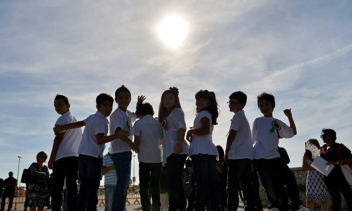 Italian elementary students attend the commemoration ceremony for the victims of the boat sinking disaster off the Lampedusa coast on Oct. 21, in San Leone near Agrigento, Italy. The disaster killed more than 300 asylum seekers. (Tullio M. Puglia/Getty Images)