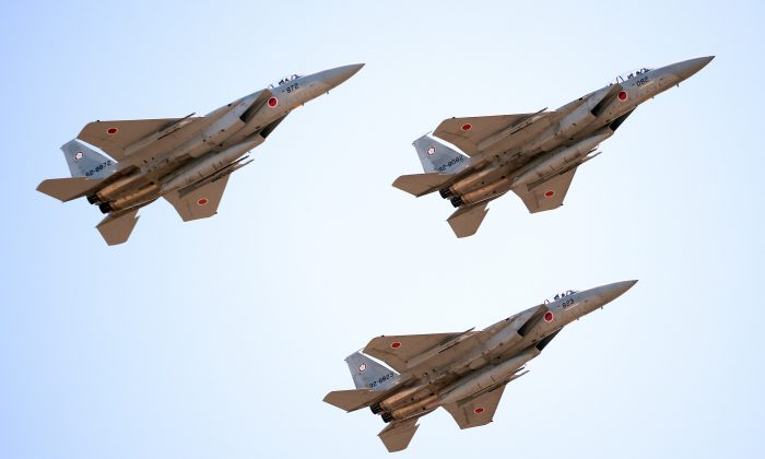 Japanese F-15 jets fly during the military review at the Ground Self-Defense Force's Asaka training ground on Oct. 27. China created an air defense zone in the East China Sea, which requires foreign jets to cooperate with Chinese authorities. (Toru Yamanaka/AFP/Getty Images)