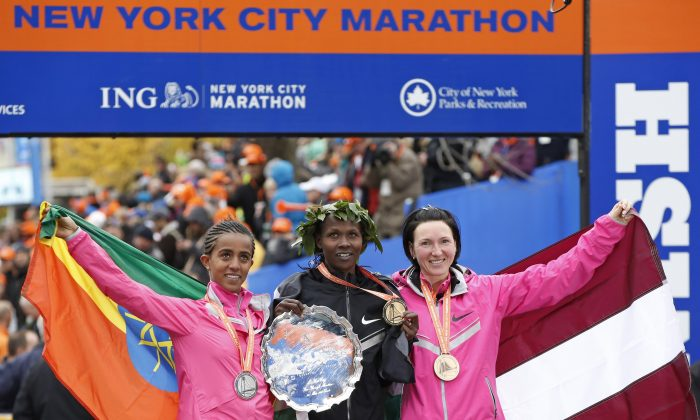 Women's winner Priscah Jeptoo of Kenya, center, second place finisher Buzunesh Deba of Ethiopia, left, and third place finisher Jelena Prokopcuka of Latvia pose with their medals after the New York City Marathon, Sunday, Nov. 3, 2013, in New York. (AP Photo/Kathy Willens)