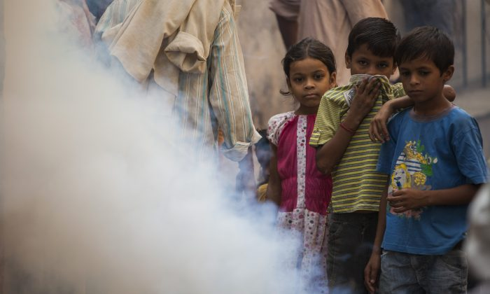 Children watch a municipal worker spray pesticide in New Delhi on Oct. 10, 2013. (Andrew Caballero-Reynolds/AFP/Getty Images)