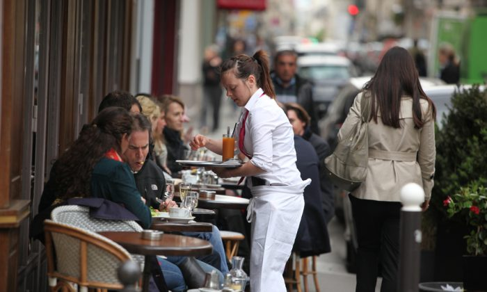 Parisians and tourist enjoy eat and drinks in cafe sidewalk in Paris, France on April 27, 2013. Paris is one of the most populated metropolitan areas in Europe.