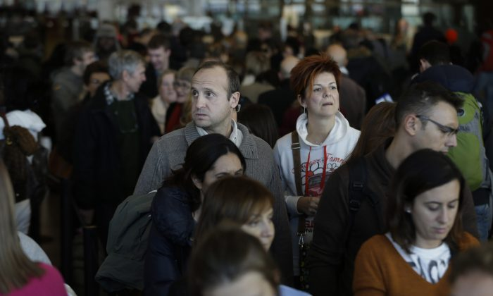 Travelers wait in a winding line to pass through customs and border control at John F. Kennedy International Airport in New York, Monday, Nov. 25, 2013. (AP Photo/Seth Wenig)