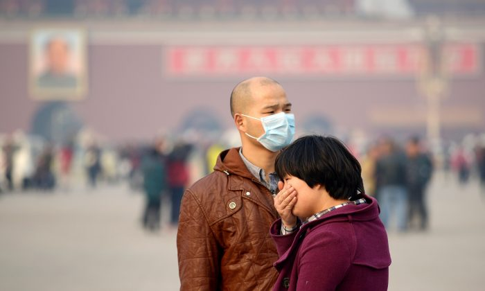 A man (L) wears a face mask as another visitor covers her mouth during a visit to Tiananmen Square in Beijing on Nov. 5, 2013. China is expected to have one million lung cancer patients by 2025 due to the effects of smoking tobacco and air pollution, according to the 6th China North-South Lung Cancer Summit hosted in Beijing Nov. 16-17. (WANG ZHAO/AFP/Getty Images)