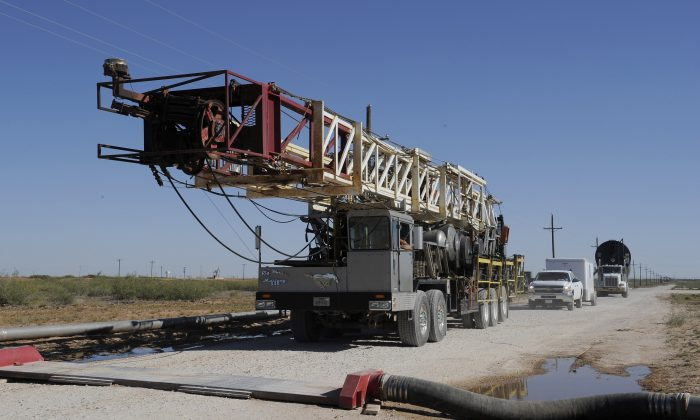 A drilling rig used for hydraulic fracturing is trucked across a water hose at a drill site Sept. 24, 2013, in Midland, Texas. The drilling method known as fracking uses huge amounts of high-pressure, chemical-laced water to free oil and natural gas trapped deep in underground rocks. With fresh water not as plentiful companies have been looking for ways to recycle their waste. (AP Photo/Pat Sullivan)