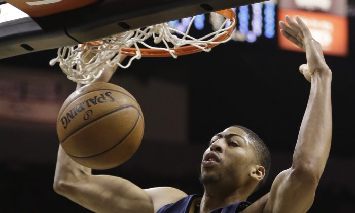New Orleans Pelicans' Anthony Davis scores against the San Antonio Spurs during the first half of an NBA basketball game, Monday, Nov. 25, 2013, in San Antonio. (AP Photo/Eric Gay)