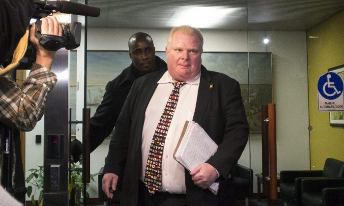 Mayor Rob Ford arrives at city hall on Tuesday, Nov. 19, 2013, in Toronto. The city council voted overwhelmingly Monday in favor of slashing Ford's office budget by 60 percent and allowing mayoral staff to join the deputy mayor, Norm Kelly. (AP Photo/The Canadian Press, Chris Young)