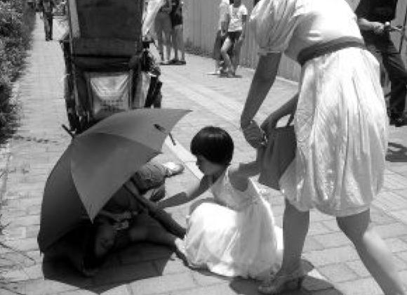 Little girl holding umbrella for ill-struck street cleaner. Fooled! (Screenshot/Secret China)