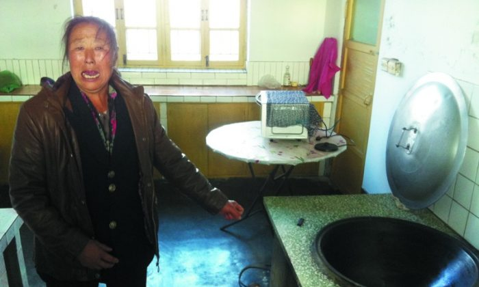 A family member of the victim showing the wok where the baby was burned. (Sohu.com)